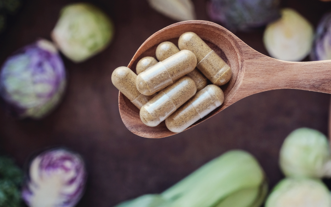 supplements on a wooden spoon surrounded by natural ingredients